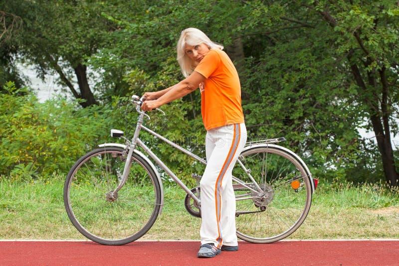 Femme supérieure avec la bicyclette photographie stock libre de droits