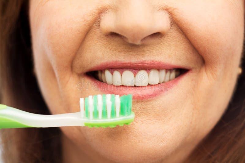 Femme supérieure avec la brosse à dents se brossant les dents images libres de droits