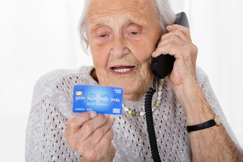 Femme supérieure avec la carte de crédit au téléphone images stock