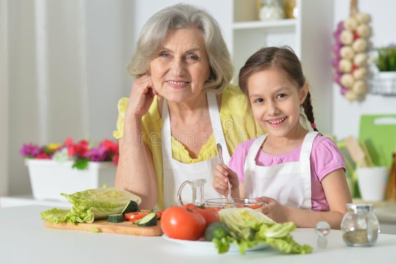 Femme supérieure avec la cuisson de petite-fille photo libre de droits