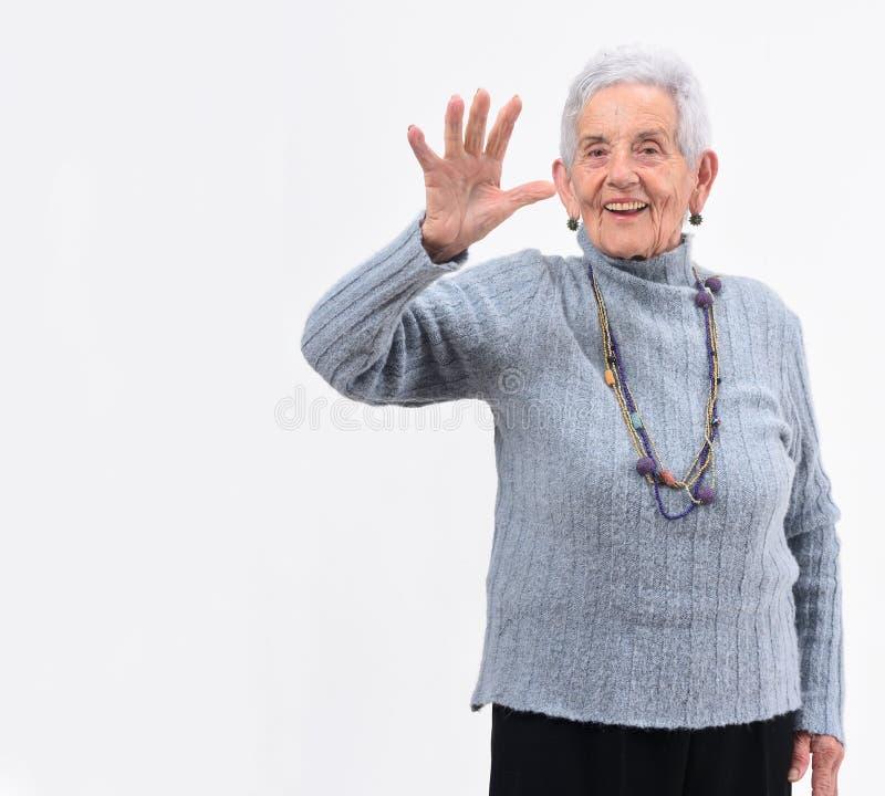 Femme supérieure avec la main et le nombre ouverts cinq sur le fond blanc images stock