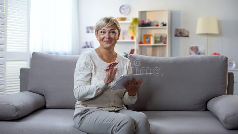 Femme supérieure avec le comprimé souriant à la caméra, achats en ligne, ventes de saison images libres de droits