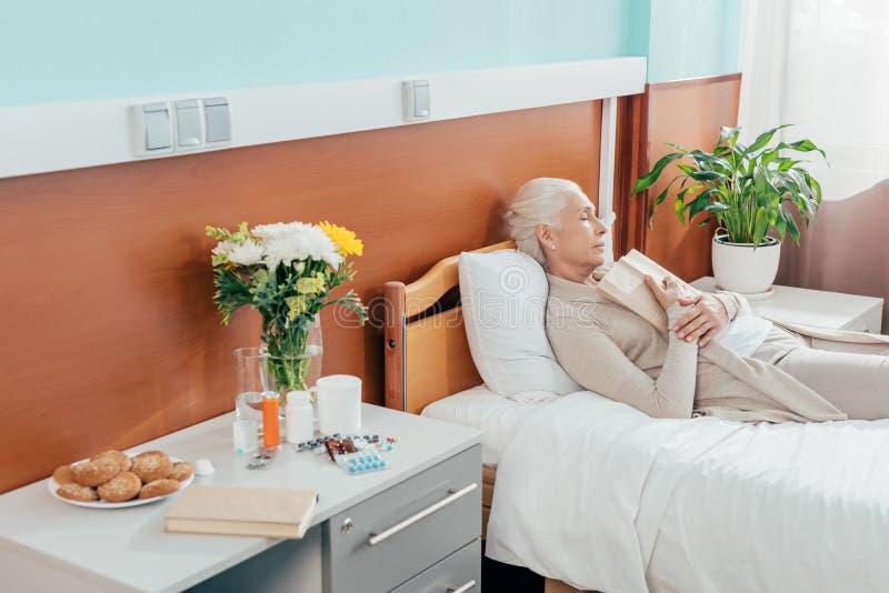 femme supérieure avec le livre dormant sur l'hôpital images stock