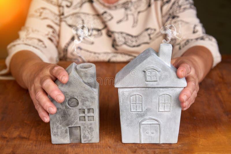 Femme supérieure avec le modèle de maison à la table Concept de soins à domicile image stock