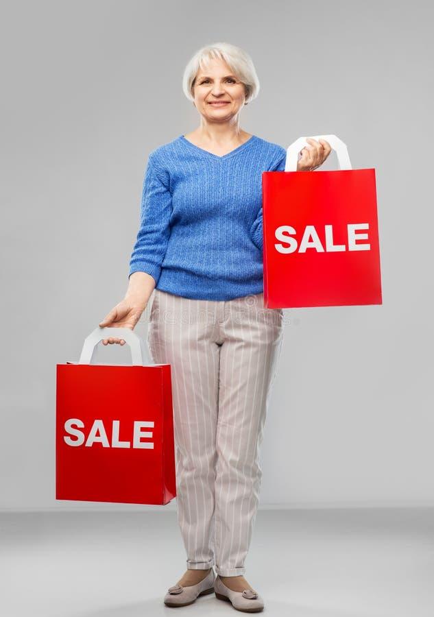 Femme supérieure avec le mot de vente sur les sacs à provisions rouges image stock