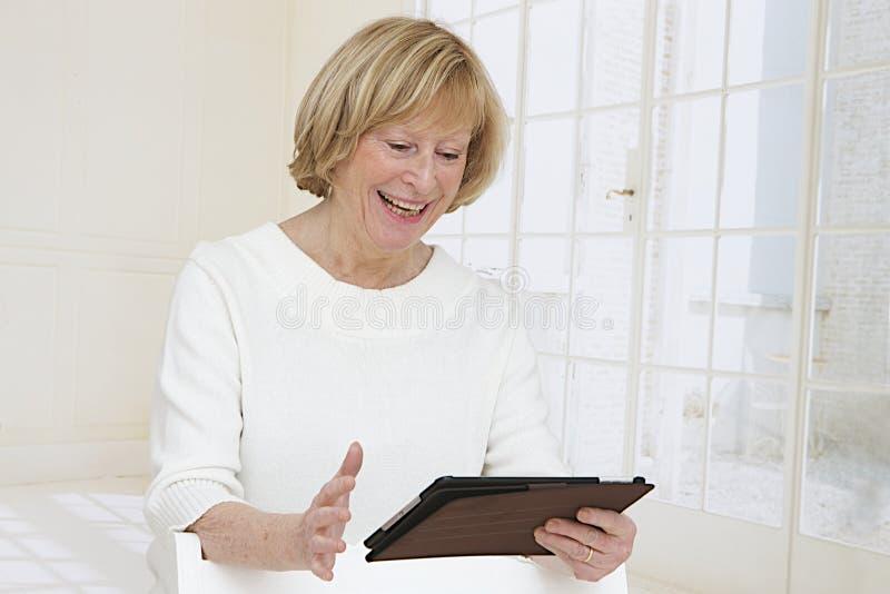 Femme supérieure avec le PC de comprimé images stock