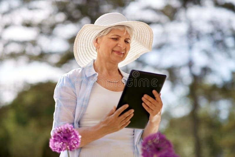 Femme supérieure avec le PC et les fleurs de comprimé au jardin images stock