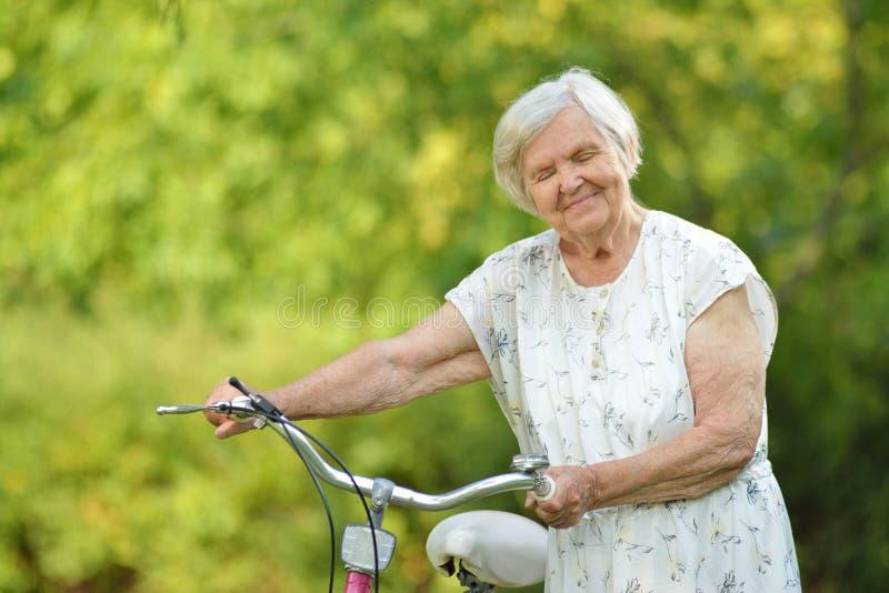 Femme supérieure avec le vélo images libres de droits