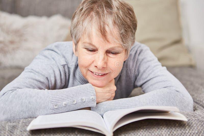 Femme supérieure avec un livre images stock