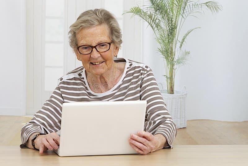 Femme supérieure ayant l'amusement sur son ordinateur photo stock