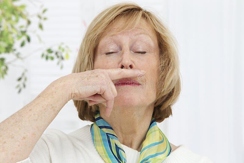 Femme supérieure ayant un rhume image stock