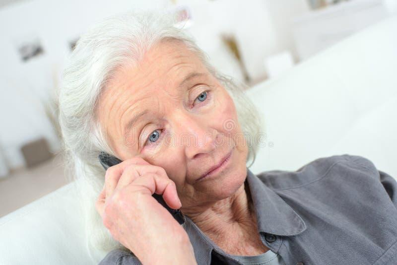 Femme supérieure bouleversée au téléphone photo stock