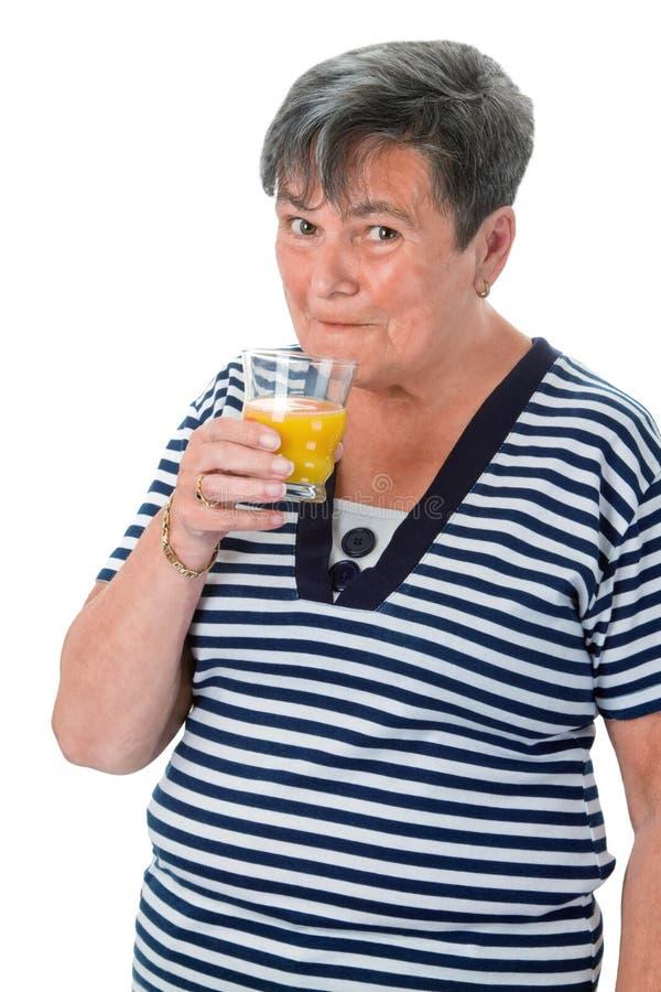 Femme supérieure buvant du jus d'orange images libres de droits