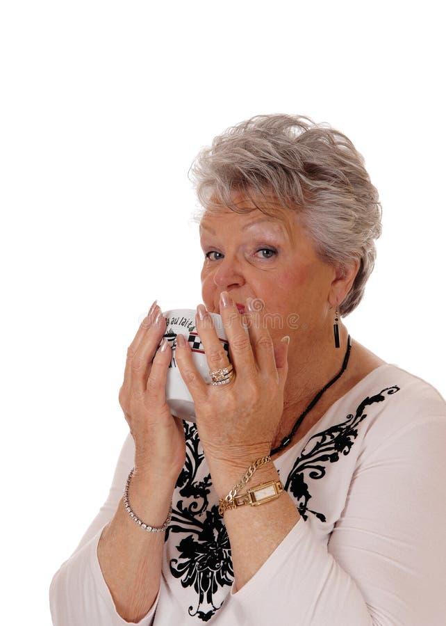 Femme supérieure buvant sa petite gorgée photo stock