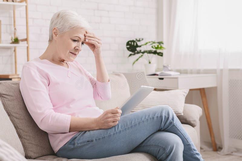 Femme supérieure confuse à l'aide de la tablette à la maison image stock
