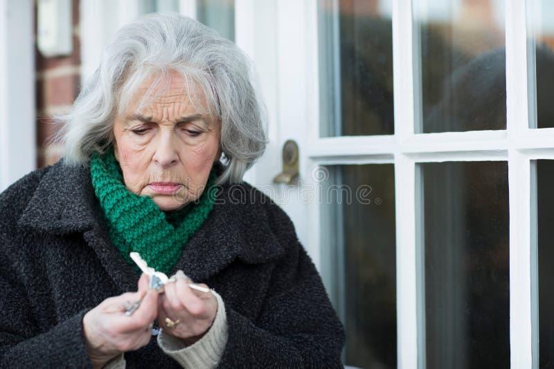 Femme supérieure confuse essayant de trouver la clé de porte image libre de droits