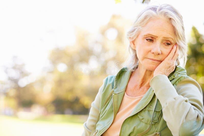 Femme supérieure déprimée s'asseyant dehors images stock