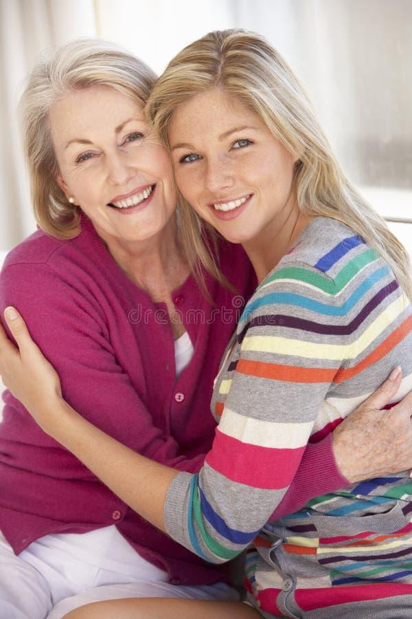 Femme supérieure détendant à la maison avec la fille adulte image stock