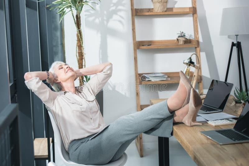 Femme supérieure d'affaires détendant avec ses jambes image stock