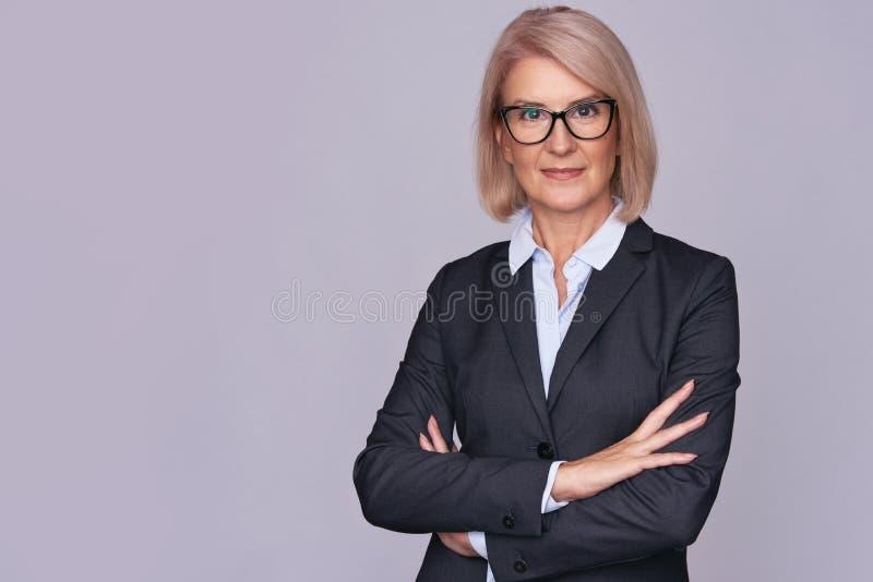 Femme supérieure d'affaires de sourire avec les mains pliées image libre de droits