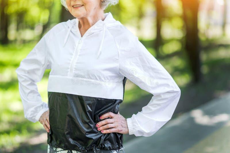 Femme supérieure d'ajustement heureux s'exerçant en parc de ville photographie stock