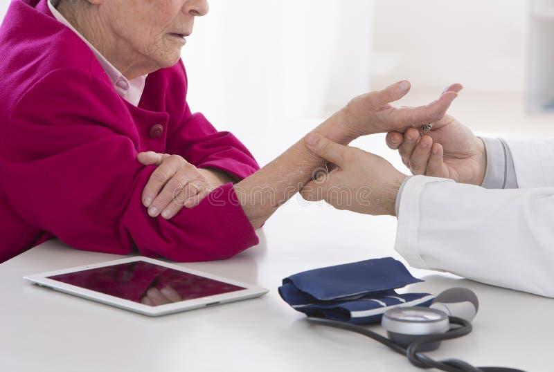 Femme supérieure d'auscultation pour la douleur de poignet photographie stock libre de droits