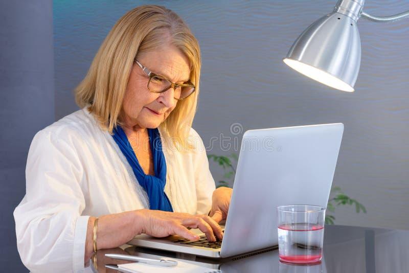 Femme supérieure dactylographiant sur l'ordinateur portable à la maison photo stock