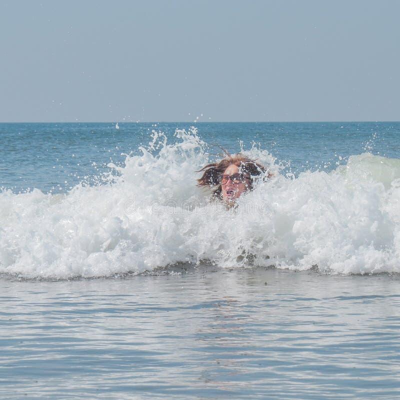 Femme supérieure dans des cris perçants en verre dans la surprise quand elle se trouve dans les profondeurs d'une onde incidente  photographie stock libre de droits
