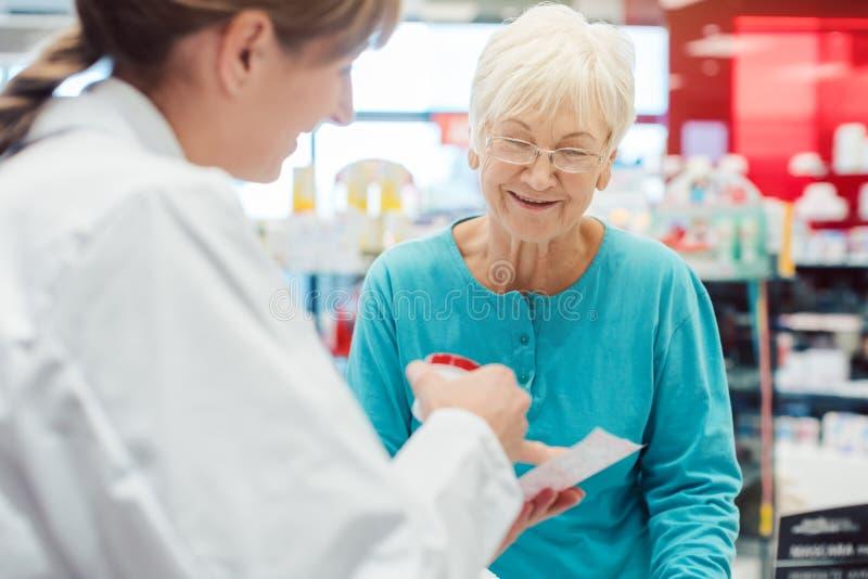 Femme supérieure dans la pharmacie parlant au chimiste ou au pharmacien images libres de droits