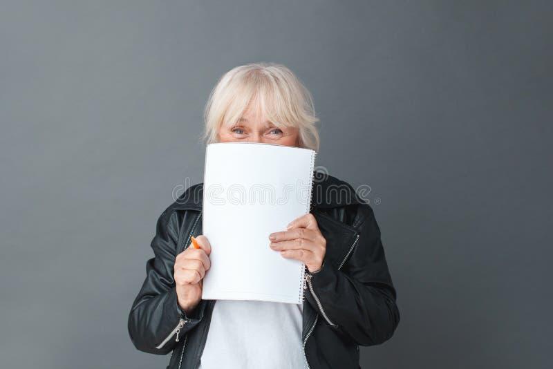 Femme supérieure dans la position de studio de veste en cuir d'isolement sur le visage de couvert gris avec le carnet regardant l photos libres de droits