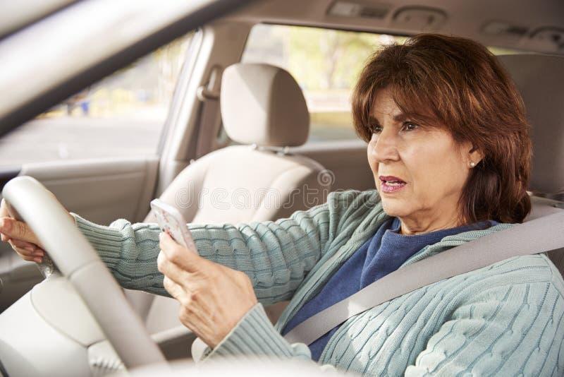 Femme supérieure dans la voiture utilisant son smartphone tout en conduisant images libres de droits