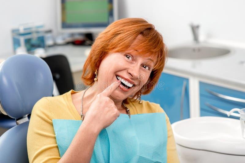Femme supérieure dans le bureau dentaire photos stock