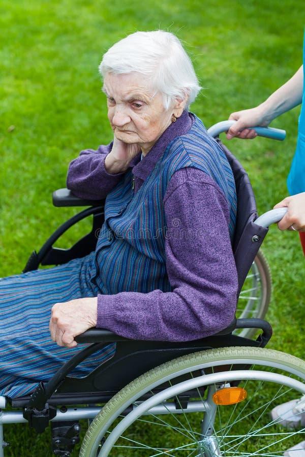 Femme supérieure dans le fauteuil roulant avec l'infirmière photos stock