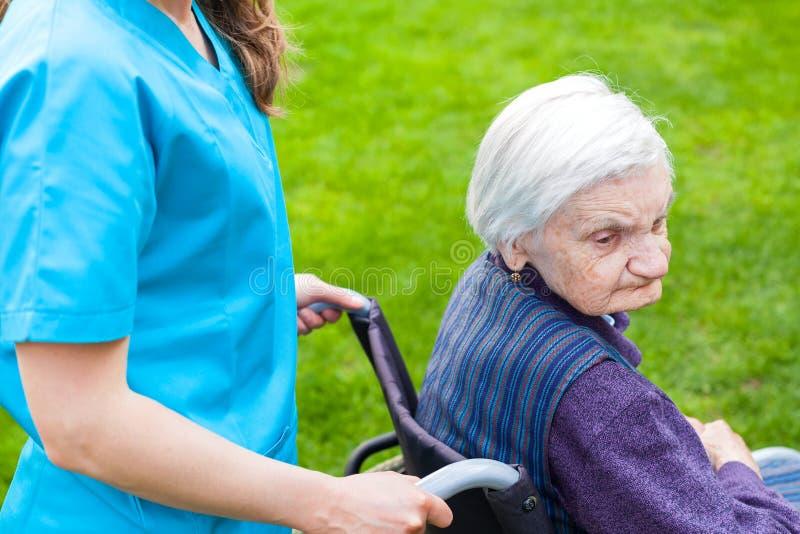 Femme supérieure dans le fauteuil roulant avec l'infirmière images stock