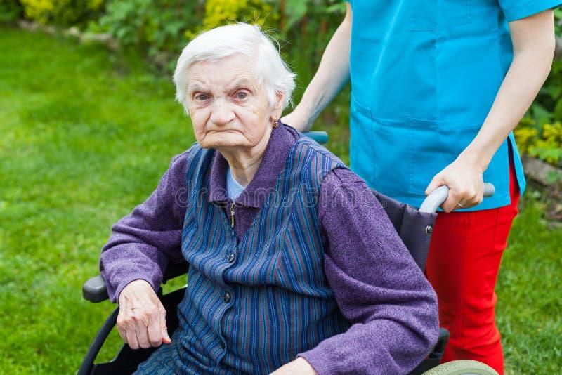 Femme supérieure dans le fauteuil roulant avec l'infirmière photographie stock