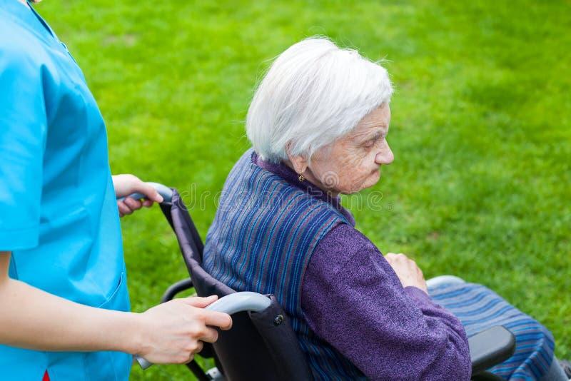 Femme supérieure dans le fauteuil roulant avec l'infirmière photos libres de droits