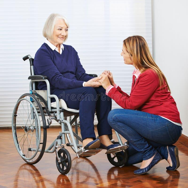 Femme supérieure dans le fauteuil roulant avec la fille images stock