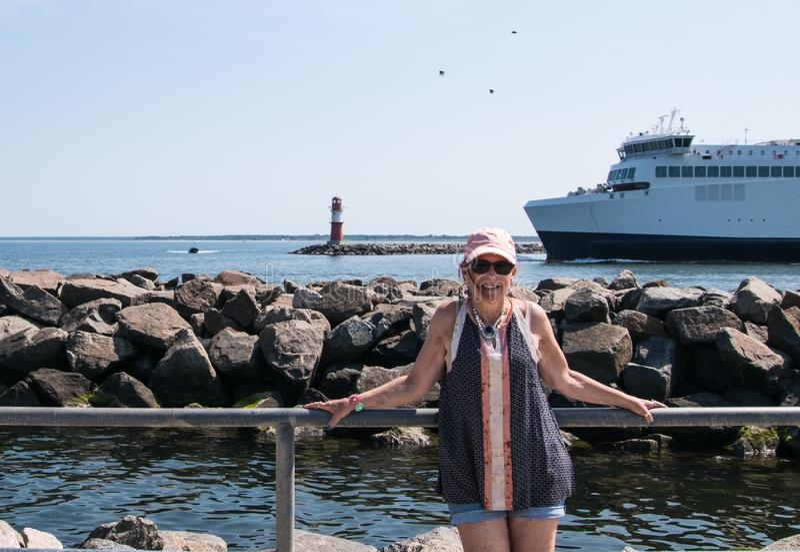 Femme supérieure de baby boomer avec le mur des roches, du grand bateau et du petit phare rouge et blanc à l'arrière-plan photos stock