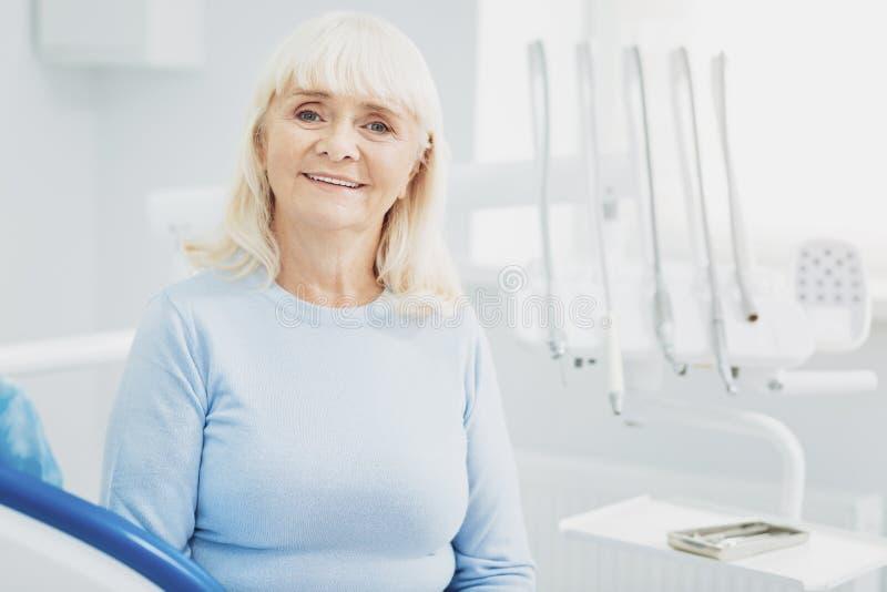 Femme supérieure de charme versant la visite sur le dentiste photographie stock