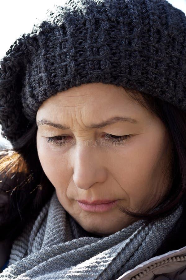 Femme supérieure de portrait dans l'écharpe et le chapeau de laine photographie stock
