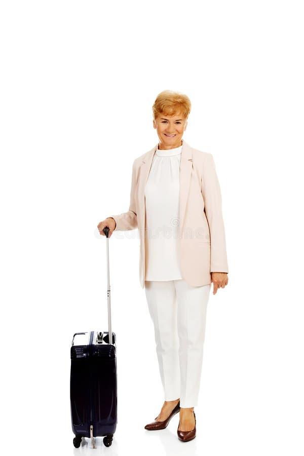 Femme supérieure de sourire avec la valise images stock