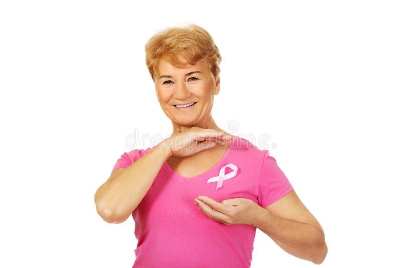 Femme supérieure de sourire avec le ruban de conscience de cancer du sein images stock
