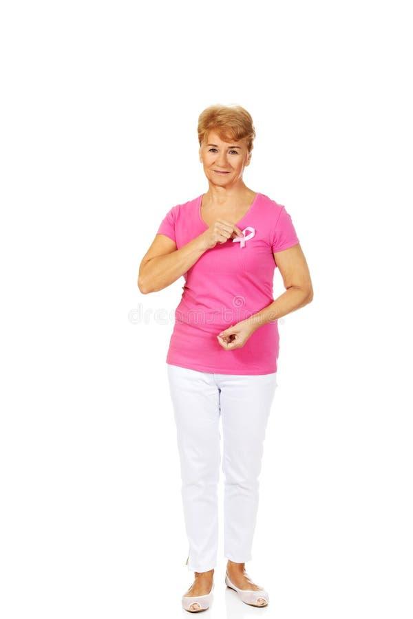 Femme supérieure de sourire avec le ruban de conscience de cancer du sein photo libre de droits