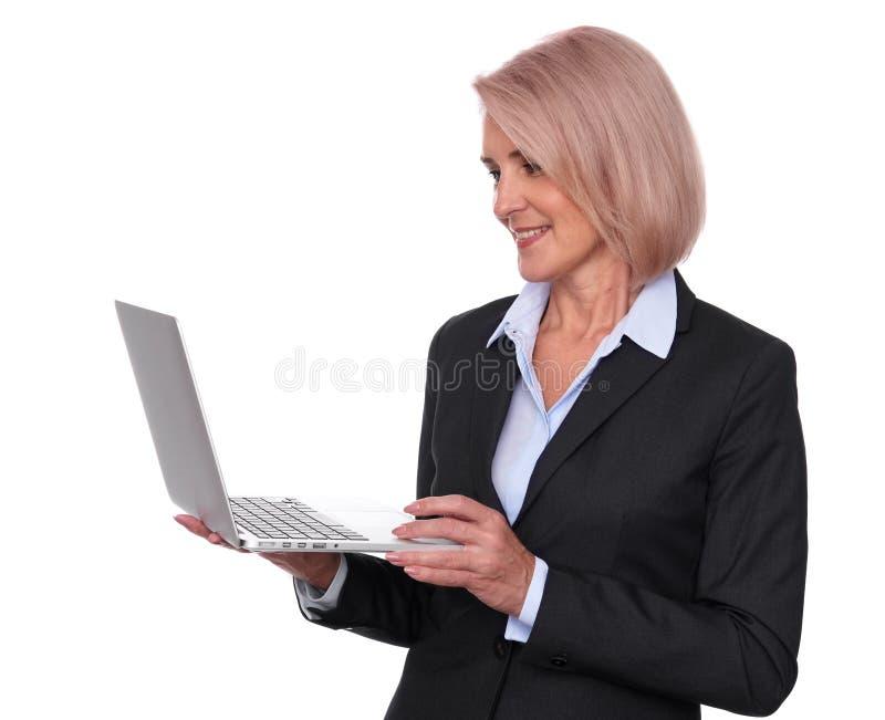 Femme supérieure de sourire d'affaires avec l'ordinateur portable image stock