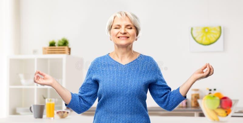 Femme supérieure de sourire heureuse méditant dans la cuisine photos libres de droits