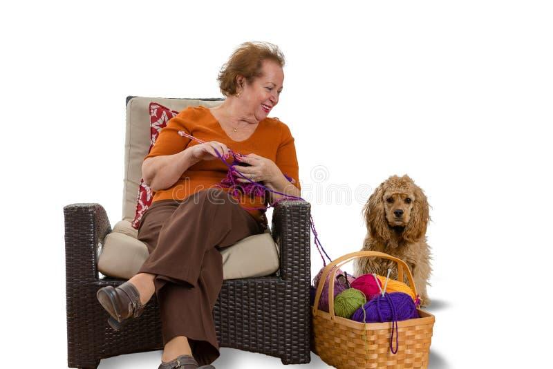 Femme supérieure de sourire heureuse tricotant avec son chien photos stock