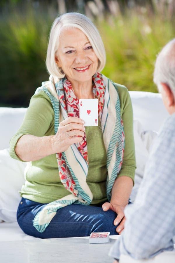 Femme supérieure de sourire jouant des cartes avec l'homme photos stock