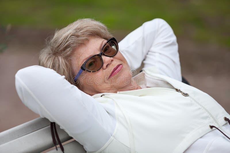 Femme supérieure de sourire se trouvant sur le banc dans le costume blanc de sports, exercices à la séance d'entraînement photo libre de droits