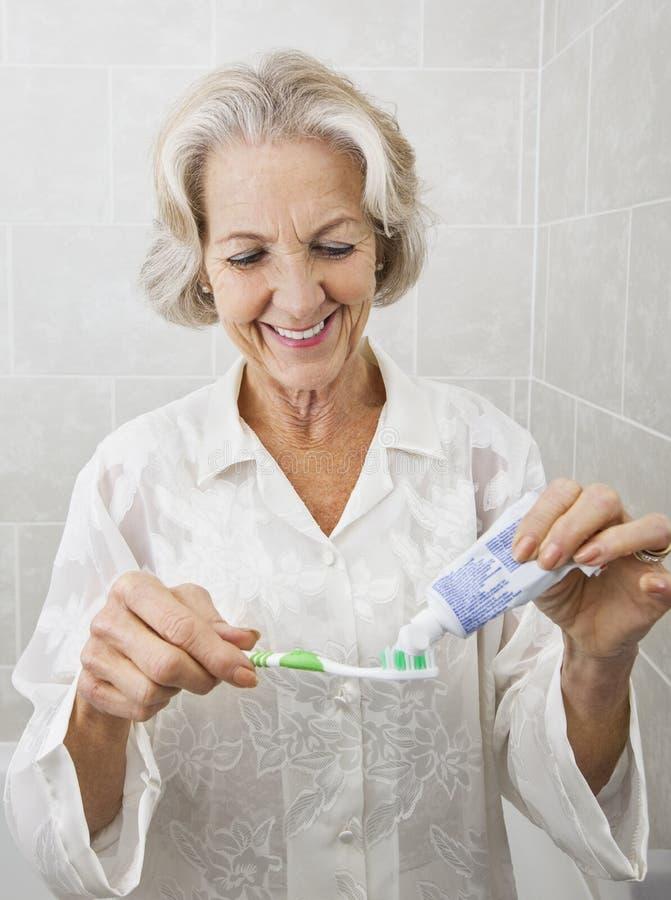 Femme supérieure de sourire serrant la pâte dentifrice sur la brosse à dents dans la salle de bains photo stock