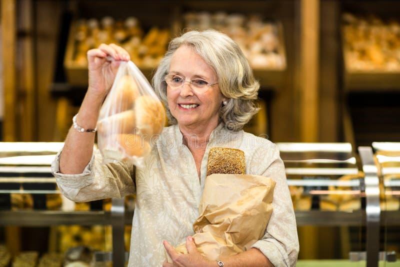 Femme supérieure de sourire tenant des sacs avec du pain images stock